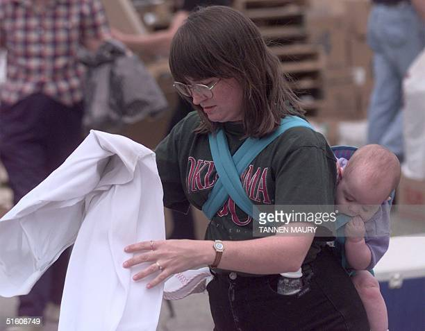 Joanne Taylor sorts donations for tornado victims at the Feed the Children distribution site in Oklahoma City OK 5 April 1999 as her 7monthold...