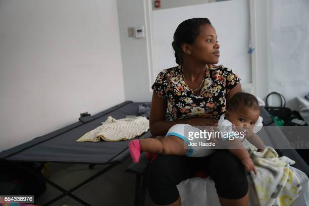 Joanne Torres sits on a cot with her daughter Eliana Heredia in the Centro de Servicios Integrados de Barrio Obrero shelter that was setup for...