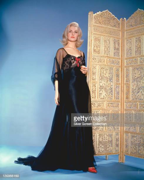 Joanne Woodward US actress wearing a long black nightgown and standing beside a folding screen with a filigree design in a studio portrait against a...