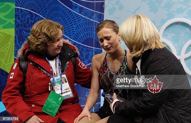 Joannie Rochette of Canada accompanied by her coach Manon Perron and doctor Julia Alleyne reacts after competing in the Ladies Short Program Figure...