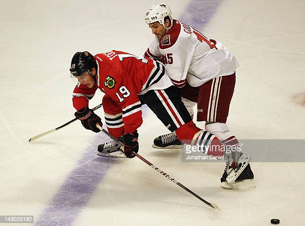 Joanthan Toews of the Chicago Blackhawks is shoved from behind by Boyd Gordon of the Phoenix Coyotes in Game Three of the Western Conference...