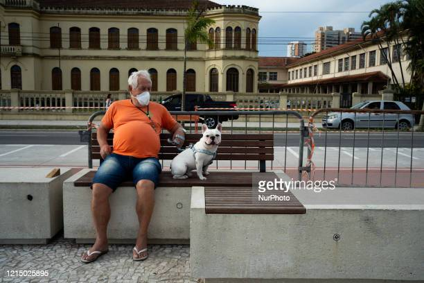 Joao 72 years old sitting on the beach boardwalk next to his dog named Latrel a French bulldog ignoring the decree that forbids access to the place...