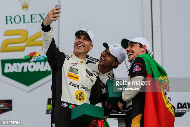 Joao Barbosa driver of the Mustang Sampling Racing Cadillac DPiVR takes a selfie in Victory Lane with teammates Filipe Albuquerque and Christian...