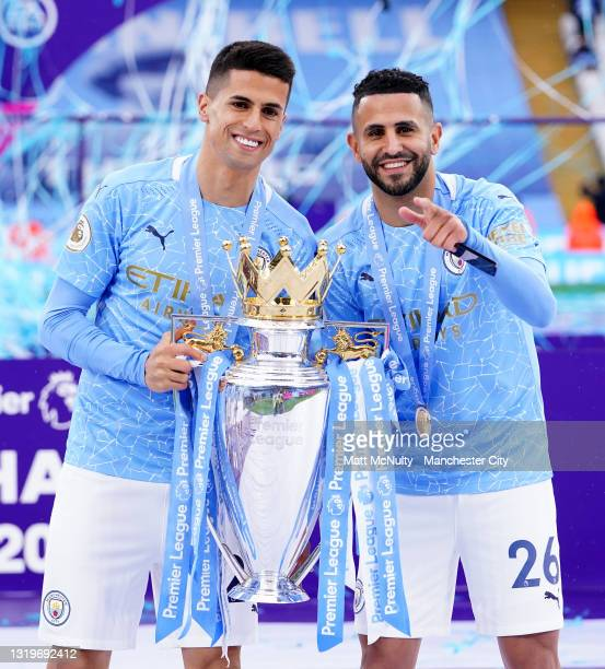 Joao Cancelo and Riyad Mahrez of Manchester City celebrate with the trophy during the Premier League match between Manchester City and Everton at...