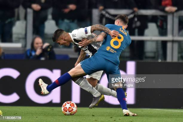 Joao Cancelo of Juventus and Saul Niguez of Atletico Madrid compete for the ball during the UEFA Champions League Round of 16 Second Leg match...