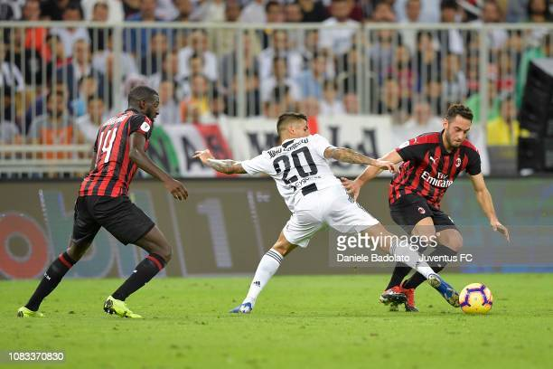 Joao Cancelo of Juventus competes for the ball with Hakan Calhanoglu of AC Milan during the Italian Supercup match between Juventus and AC Milan at...