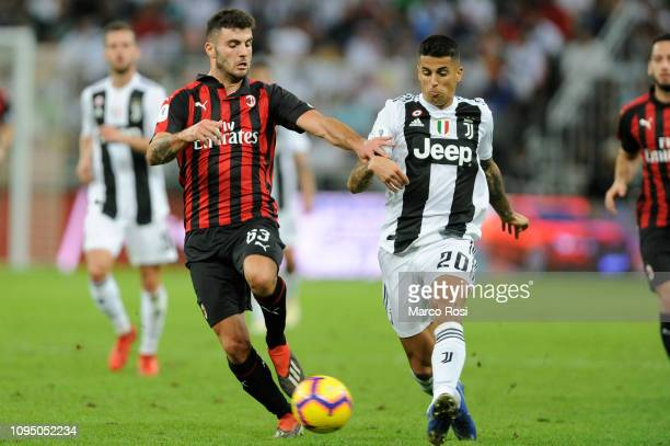 Joao Cancelo of Juventus competes for the ball with Patrick Cutrone of AC Milan during the Italian Supercup match between Juventus and AC Milan at...