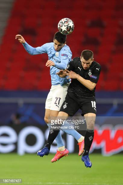 Joao Cancelo of Manchester City battles for a header with Laszlo Benes of Borussia Moenchengladbach during the UEFA Champions League Round of 16...