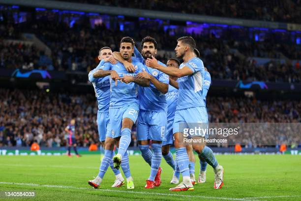 Joao Cancelo of Manchester City celebrates with teammate Ilkay Guendogan and Ruben Dias after scoring their side's fifth goal during the UEFA...