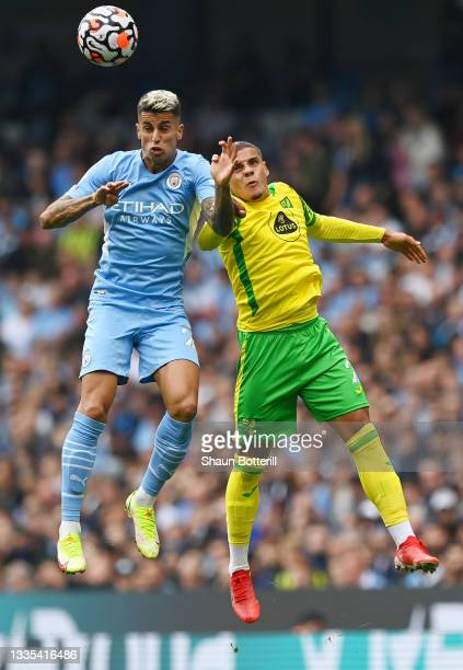 Joao Cancelo of Manchester City competes for a header with Max Aarons of Norwich City during the Premier League match between Manchester City and...