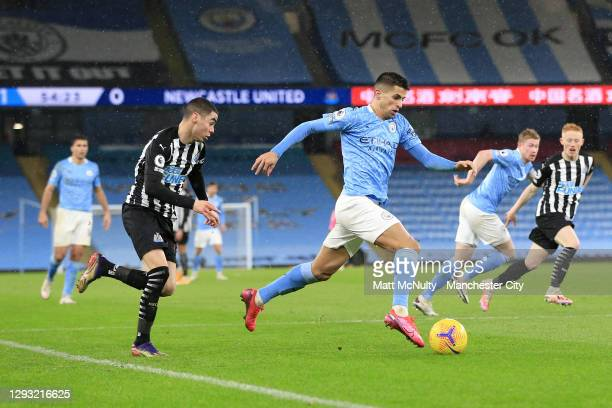 Joao Cancelo of Manchester City runs with the ball under pressure from Miguel Almiron of Newcastle United during the Premier League match between...