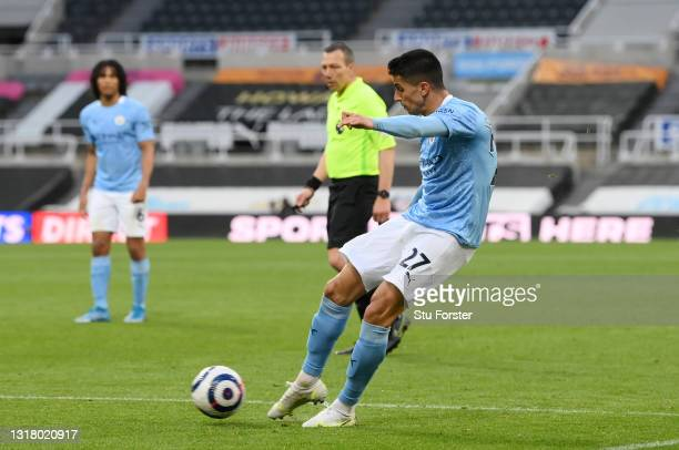 Joao Cancelo of Manchester City scores their side's first goal during the Premier League match between Newcastle United and Manchester City at St....