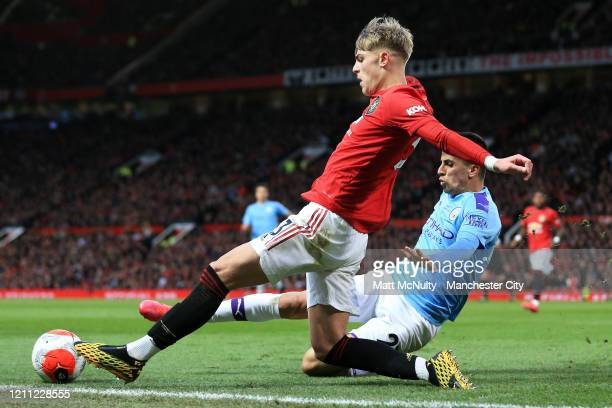 Joao Cancelo of Manchester City tackles Brandon Williams of Manchester United during the Premier League match between Manchester United and...