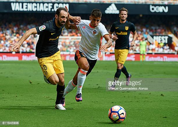Joao Cancelo of Valencia competes for the ball with Juanfran Torres of Atletico de Madrid during the La Liga match between Valencia CF and Atletico...