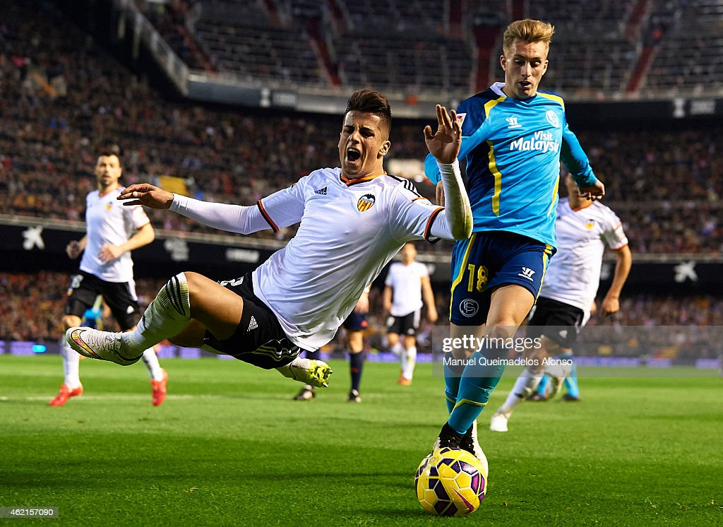 Joao Cancelo of Valencia is tackled by Gerard Deulofeu of Sevilla during the La Liga match between Valencia CF and Sevilla FC at Estadi de Mestalla on January 25, 2015 in Valencia, Spain.