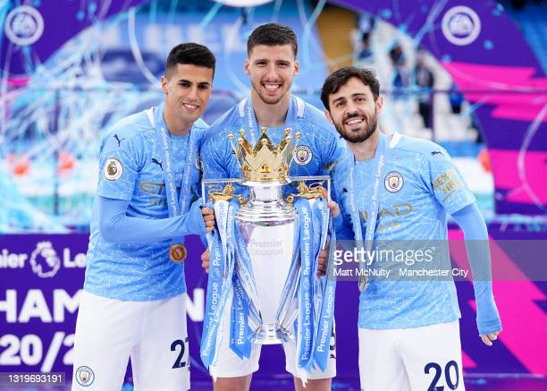 Joao Cancelo, Ruben Dias and Bernardo Silva of Manchester City celebrate with the trophy during the Premier League match between Manchester City and...