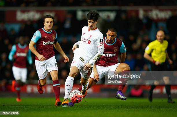 Joao Carlos Teixeira of Liverpool evades Mark Noble and Winston Reid of West Ham United during the Emirates FA Cup Fourth Round Replay match between...