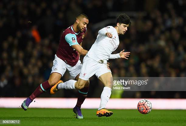 Joao Carlos Teixeira of Liverpool evades Winston Reid of West Ham United during the Emirates FA Cup Fourth Round Replay match between West Ham United...
