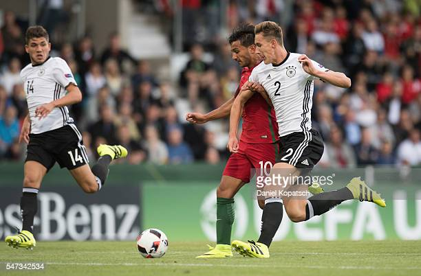 Joao Carvalho of Portugal is challenged by Phil Neumann of Germany during the UEFA Under19 European Championship match between U19 Germany and u19...