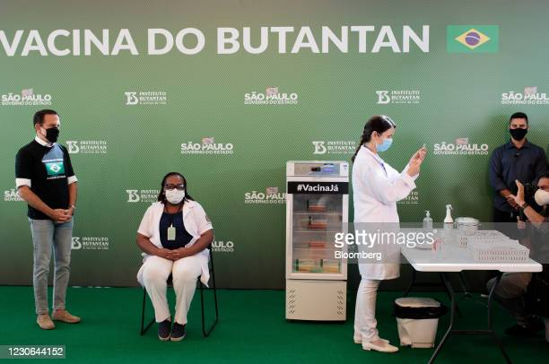 Joao Doria, governor of Sao Paulo, watches as Jessica Pires de Camargo, master of public health at Santa Casa de Sao Paulo, right, prepares the first...
