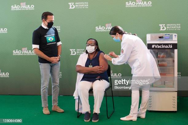 Joao Doria, governor of Sao Paulo, watches as Jessica Pires de Camargo, master of public health at Santa Casa de Sao Paulo, right, administers the...