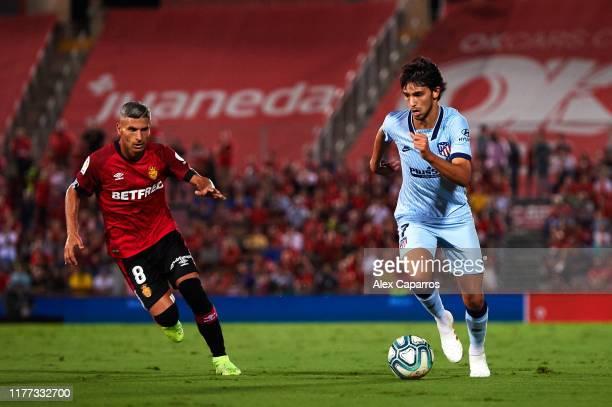 Joao Felix of Atletico de Madrid runs with the ball under pressure from Salva Sevilla of RCD Mallorca during the La Liga match between RCD Mallorca...