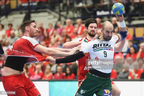 Joao Ferraz of Wetzlar is challenged by Gunnar Dietrich and Jonathan Scholz of Ludwigshafen during the DKB HBL match between Die Eulen Ludwigshafen...