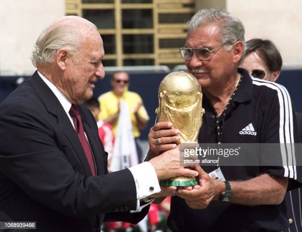 Joao Havelange the departing President of the World Soccer Federation hands over a replica of the world cup to former Mexican goalkeeper Antonio...