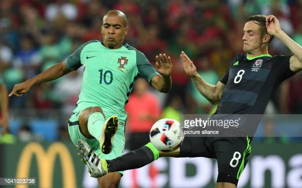 Joao Mario of Portugal and Andy King of Wales vie for the ball during the UEFA EURO 2016 semi final soccer match between Portugal and Wales at the...