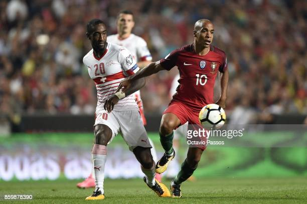 Joao Mario of Portugal competes for the ball with Johan Djourou of Switzerland during the FIFA 2018 World Cup Qualifier between Portugal and...