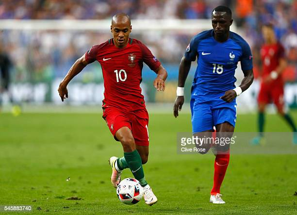Joao Mario of Portugal in action with Moussa Sissoko of France during the UEFA EURO 2016 Final match between Portugal and France at Stade de France...