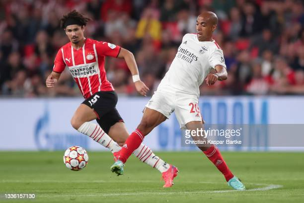 Joao Mario of SL Benfica is tackled by Andre Ramalho of PSV Eindhoven during the UEFA Champions League Play-Offs Leg Two match between PSV Eindhoven...