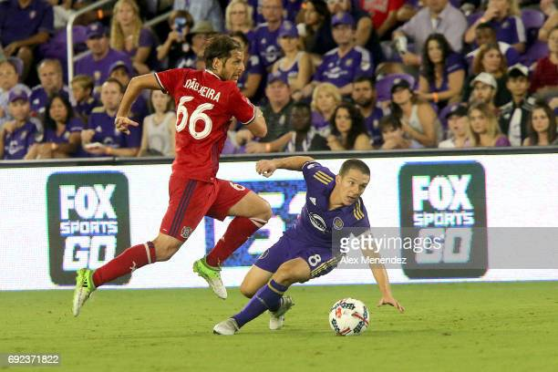 Joao Meira of Chicago Fire runs past a falling Will Johnson of Orlando City SC during a MLS soccer match between the Chicago Fire and the Orlando...