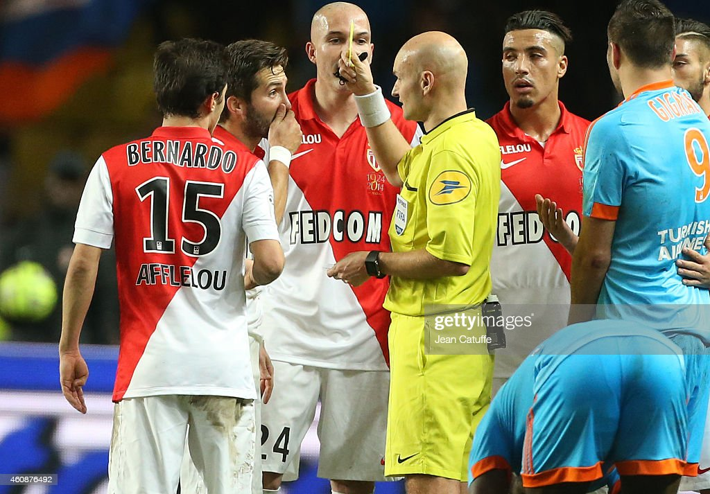Joao Moutinho of Monaco receives a yellow card from referee Tony Chapron during the French Ligue 1 match between AS Monaco FC v Olympique de Marseille OM at Stade Louis II on December 14, 2014 in Monaco.