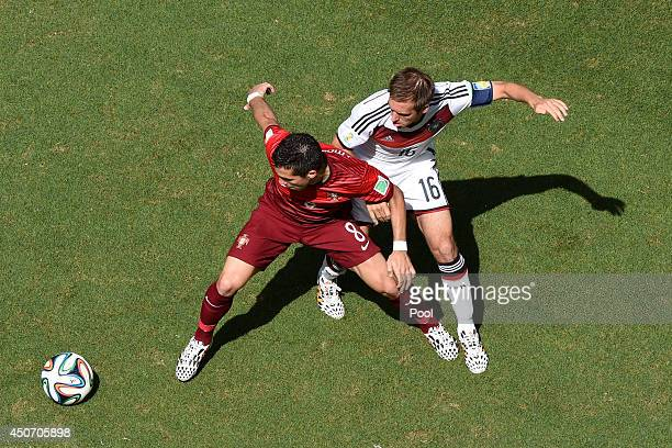 Joao Moutinho of Portugal holds off a challenge by Philipp Lahm of Germany during the 2014 FIFA World Cup Brazil Group G match between Germany and...
