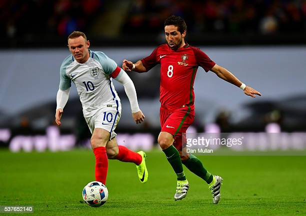 Joao Moutinho of Portugal is chased by Wayne Rooney of England during the international friendly match between England and Portugal at Wembley...