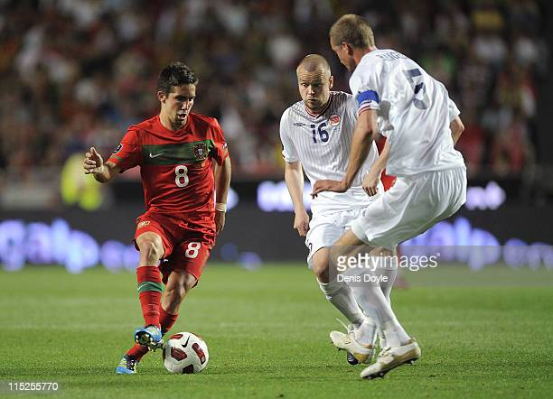 Joao Moutinho of Portugal takes on Brede Hangeland and Christian Grindheim of Norway during the EURO 2012 Group H qualifier between Portugal and...