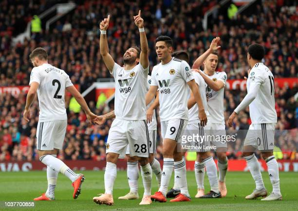 Joao Moutinho of Wolverhampton Wanderers celebrates after scoring his team's first goal with his team mates during the Premier League match between...