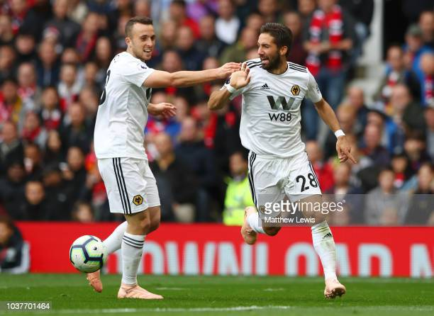 Joao Moutinho of Wolverhampton Wanderers celebrates with teammate Diogo Jota after scoring his team's first goal during the Premier League match...