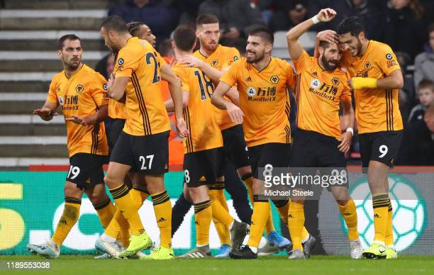 Joao Moutinho of Wolverhampton Wanderers celebrates with teammates after scoring his team's first goal during the Premier League match between AFC...