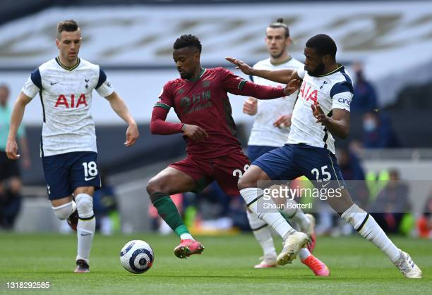 Joao Moutinho of Wolverhampton Wanderers is challenged by Giovani Lo Celso and Japhet Tanganga of Tottenham Hotspur during the Premier League match...