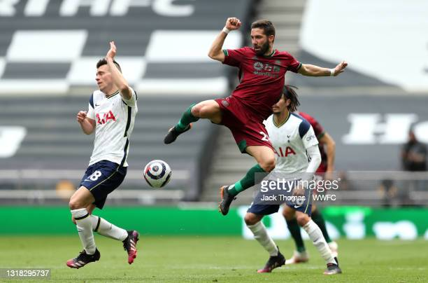 Joao Moutinho of Wolverhampton Wanderers jumps for the ball with Giovani Lo Celso of Tottenham Hotspur during the Premier League match between...