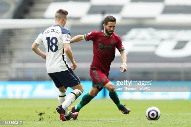 Joao Moutinho of Wolverhampton Wanderers runs with the ball under pressure from Giovani Lo Celso of Tottenham Hotspur during the Premier League match...
