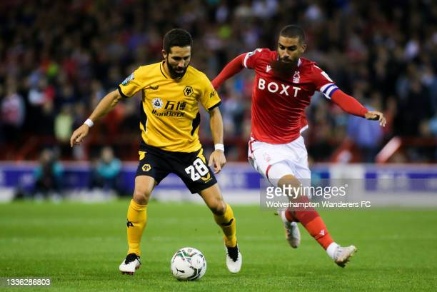Joao Moutinho of Wolverhampton Wanderers runs with the ball under pressure from Lewis Grabban of Nottingham Forest during the Carabao Cup Second...