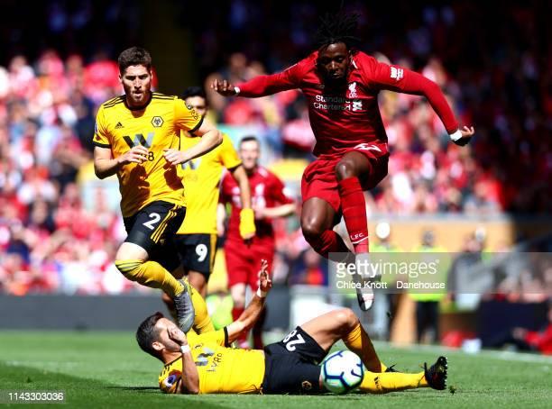 Joao Moutinho of Wolverhampton Wanderers tackles Divock Origi of Liverpool during the Premier League match between Liverpool FC and Wolverhampton...