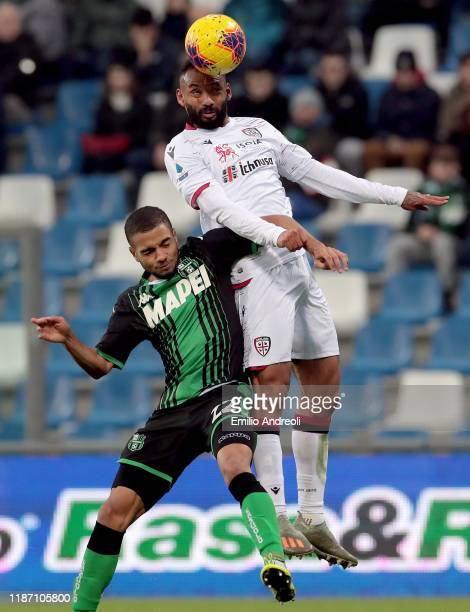 Joao Pedro of Cagliari Calcio jumps for the ball against Jeremy Toljan of US Sassuolo and scores his goal during the Serie A match between US...