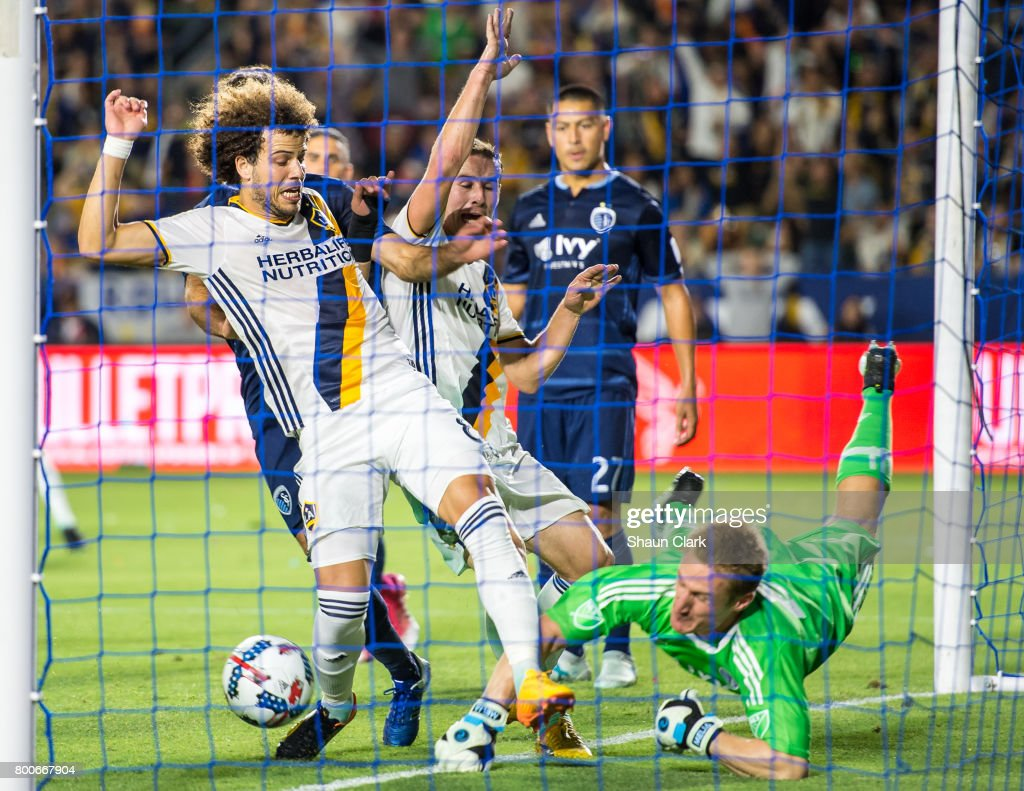 Joao Pedro #8 of Los Angeles Galaxy follows a header by Dave Romney #4 of Los Angeles Galaxy into the net as Tim Melia #29 of Sporting Kansas City tries to make a save during the Los Angeles Galaxy's MLS match against Sporting KC at the StubHub Center on June 24, 2017 in Carson, California. Sporting Kansas City won the match 2-1