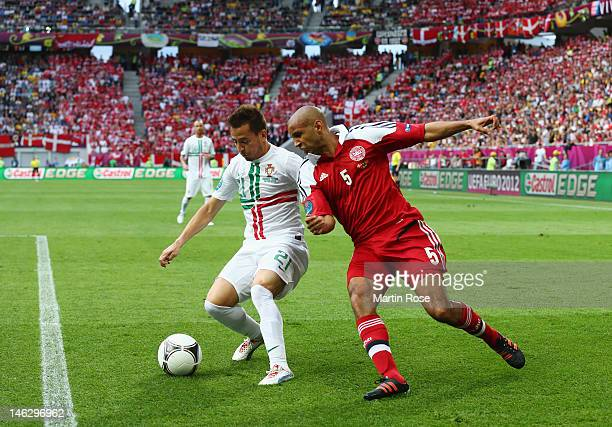 Joao Pereira of Portugal and Simon Poulsen of Denmark compete for the ball during the UEFA EURO 2012 group B match between Denmark and Portugal at...