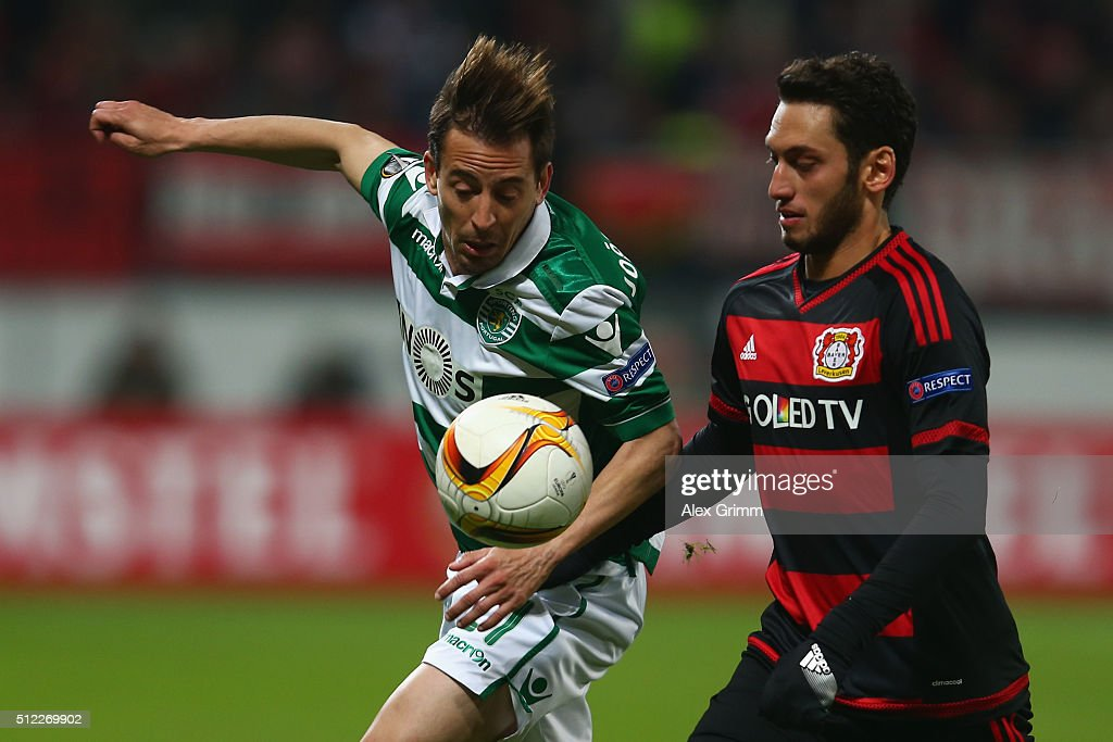Joao Pereira (L) of Sporting is challenged by Hakan Calhanoglu of Leverkusen during the UEFA Europa League round of 32 second leg match between Bayer Leverkusen and Sporting Lisbon at BayArena on February 25, 2016 in Leverkusen, Germany.