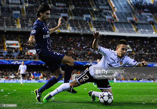 Joao Pereira of Valencia CF duels for the ball with Javier Pastore of Paris SaintGermain during the UEFA Champions League Round of 16 first leg match...
